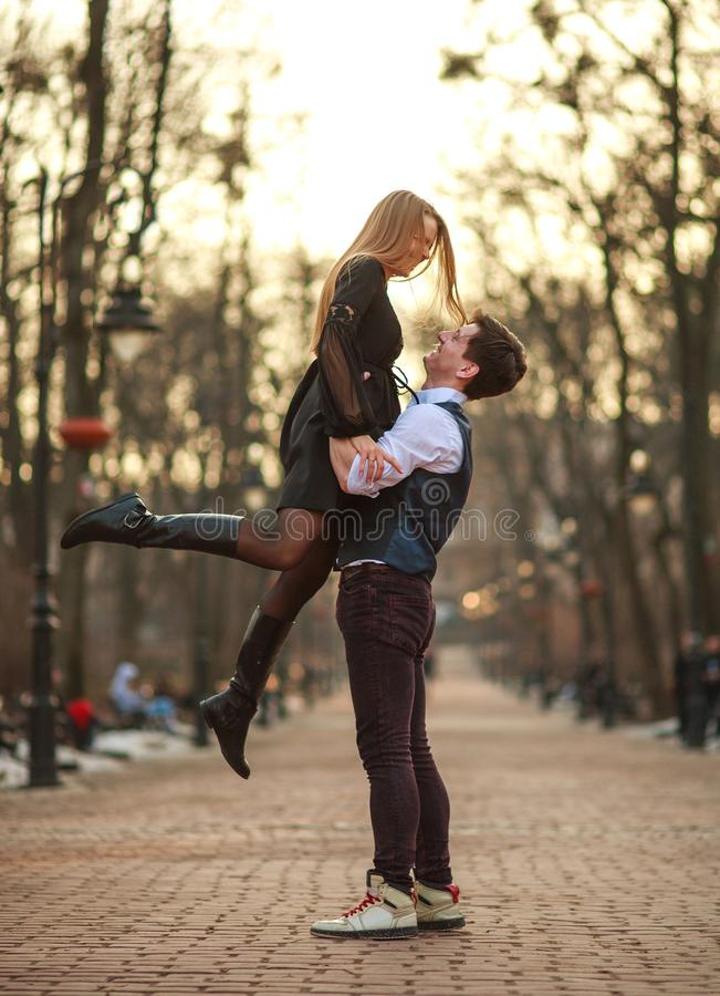 Elegant young couple in love in classic style passionately dancing in city park royalty free stock image