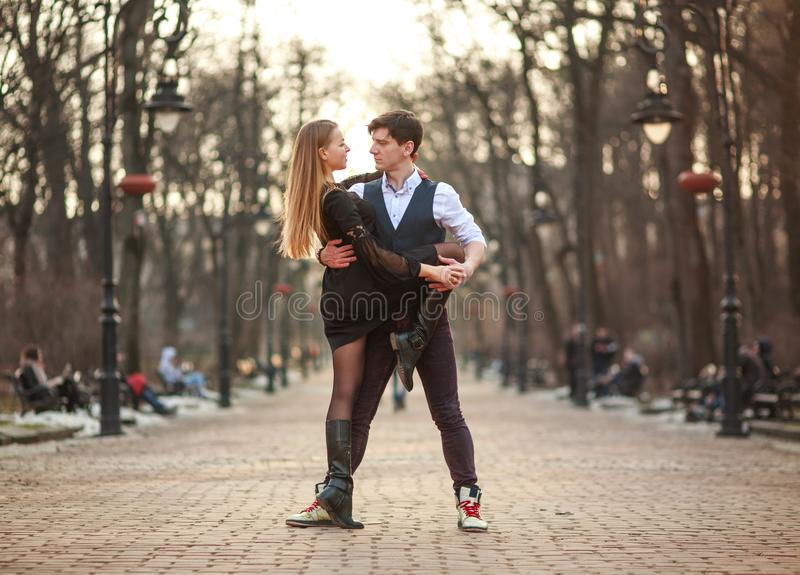 Elegant young couple in love in classic style passionately dancing in city park royalty free stock photos