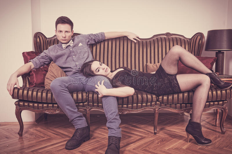 Elegant young couple in love lying and sitting on a vintage couch stock photo