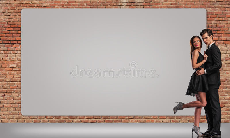 Elegant young couple standing embraced near big billboard stock image