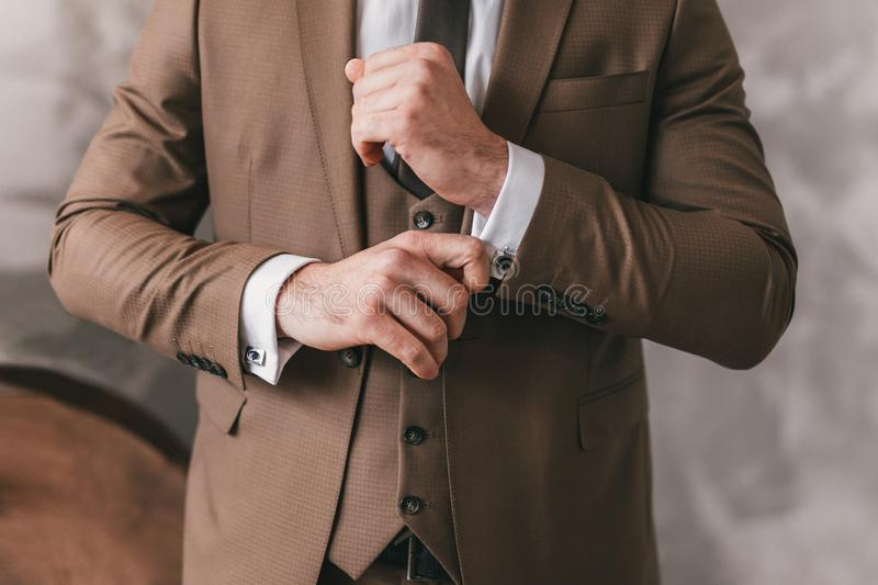 Elegant young fashion man looking at his cufflinks while fixing them. Photo of male hands. Handsome groom dressed in brown formal stock images