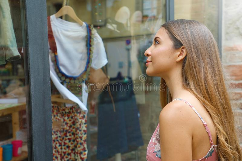Elegant young fashion woman looking at showcase of clothing store stock images