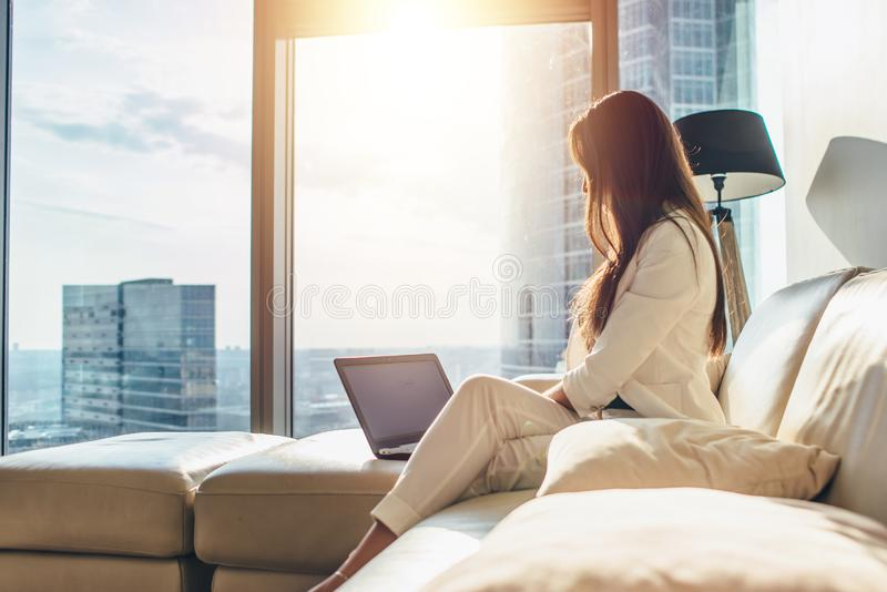 Elegant young female business woman using a laptop sitting on a sofa at home.  stock photography