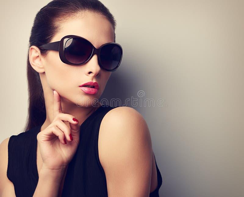 Elegant young female model in trendy sunglasses posing. Vintage stock photo