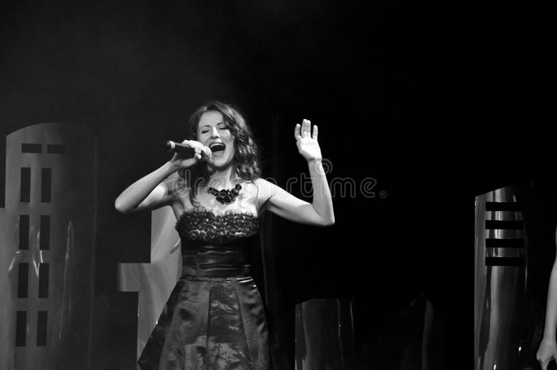Elegant young female singer in black dress holding microphone, live performance, concert, unrecognizable person. black and white stock images