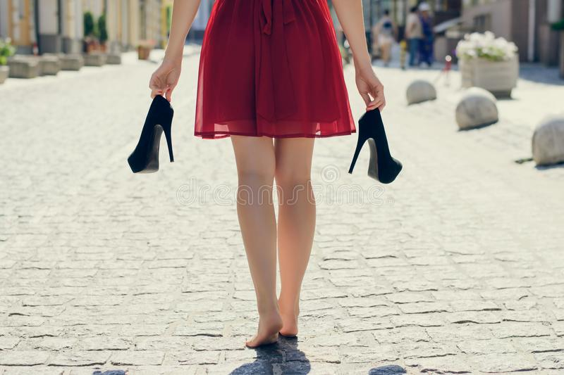 Elegant young girl in red dress with high-heels in hands, walking on the street barefoot. She is coming back home after party in royalty free stock photos