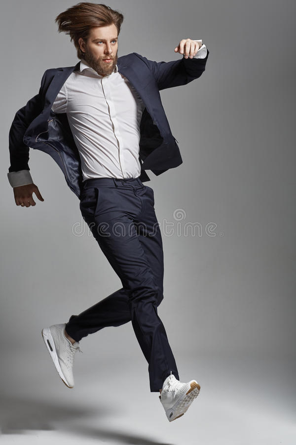 Elegant young guy jumping and dancing royalty free stock photo