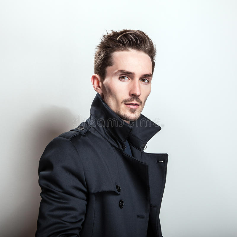 Elegant young handsome man in long stylish dark blue coat. Studio fashion portrait stock images