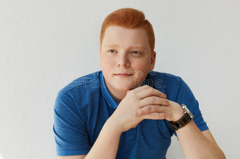 An elegant young handsome man with red hair and freckles wearing blue shirt and watch holding his hands together isolated over whi. Te background dreaming about stock image