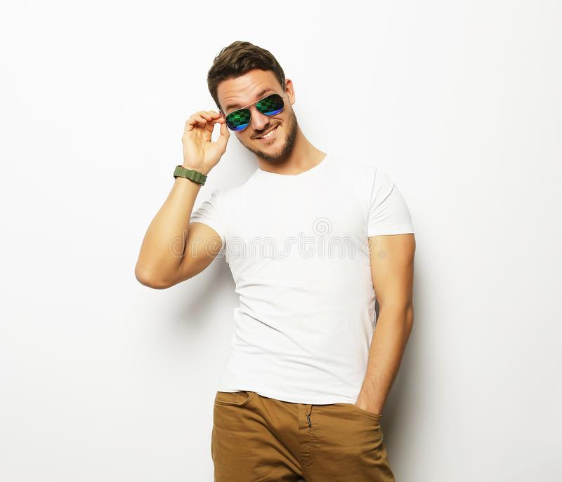 Elegant young handsome manin smart casual wear and sunglasses. royalty free stock image