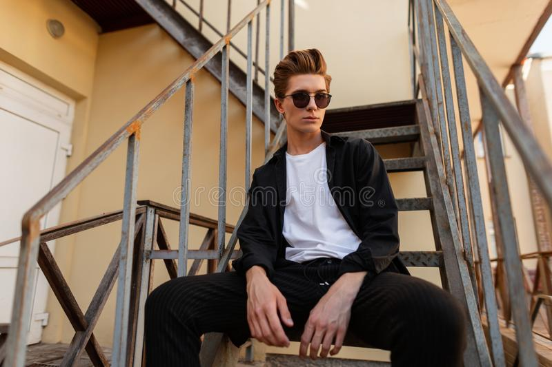 Elegant young hipster man sitting on the iron stairs. Attractive guy model in fashionable clothes in trendy sunglasses. With a stylish hairstyle rest outdoors royalty free stock photos
