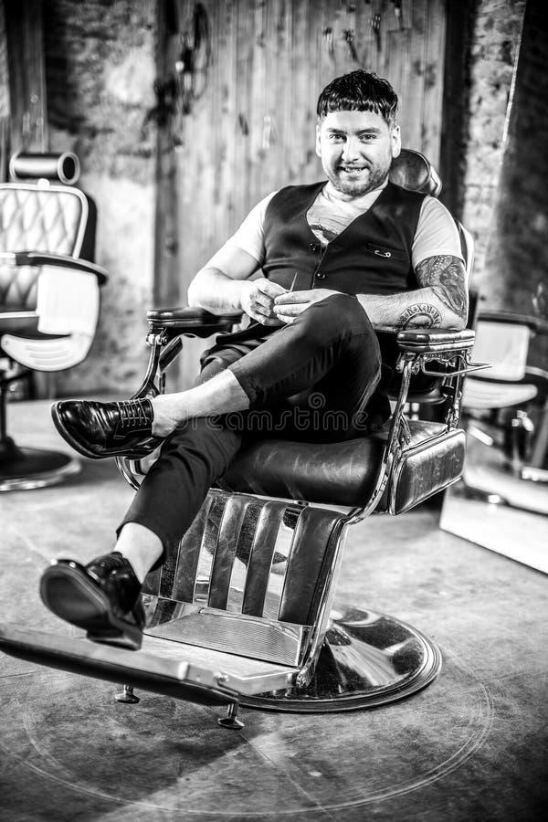Elegant young man in barbershop. Black-white photo. stock photos
