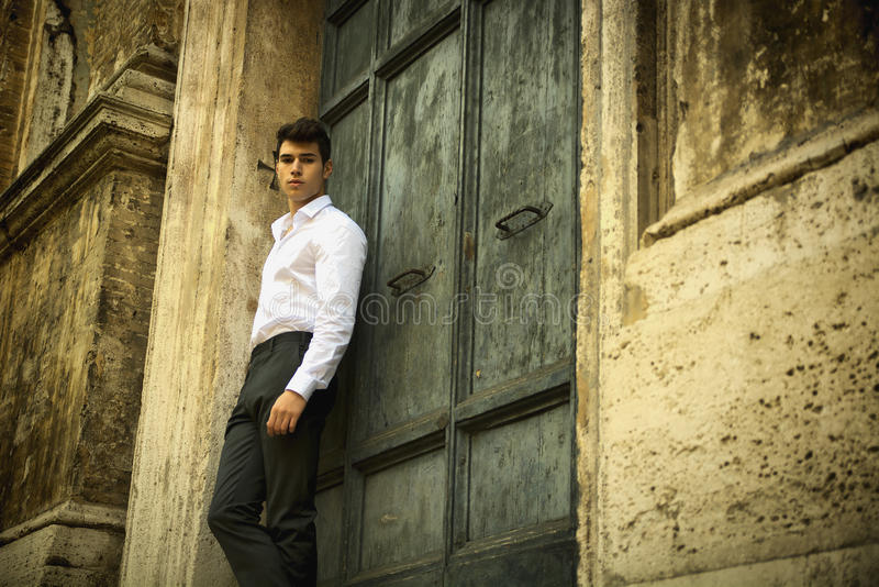 Elegant young man leaning against old wall and door stock photos