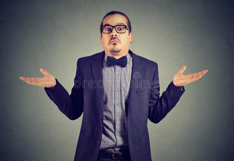 Elegant young man looking ignorant. Young man in formal clothing shrugging shoulders while posing on gray and looking confused stock photo