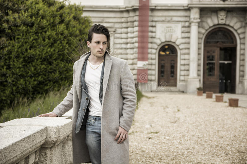 Elegant young man outdoor wearing wool coat royalty free stock photography