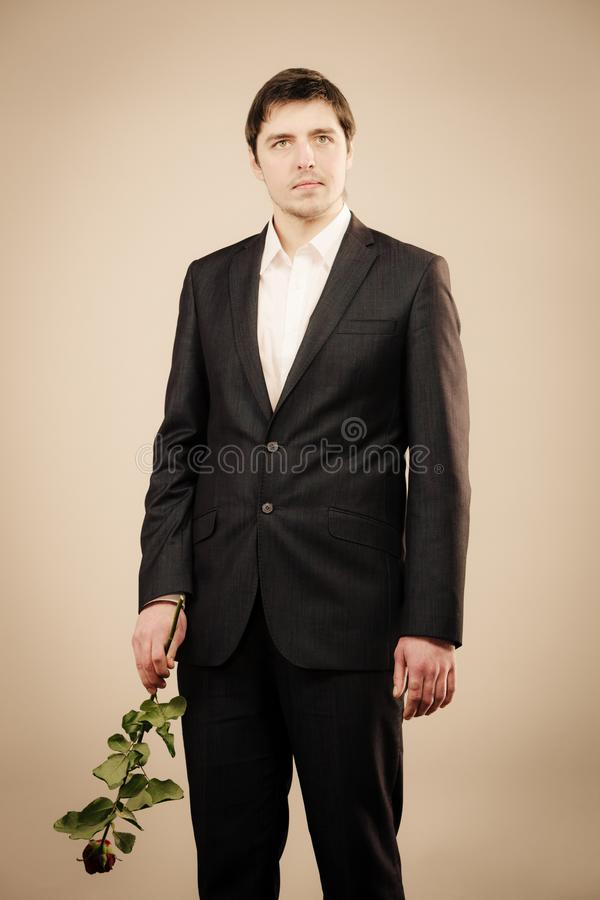 Elegant young man with red rose. stock photos