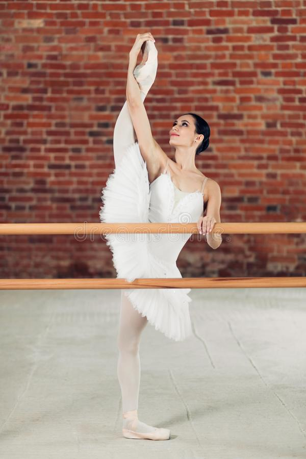 Elegant young smiling woman in tutu stretching legs in dance class royalty free stock photos