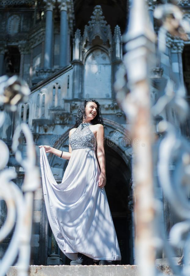An elegant young woman in a ball gown next to a castle royalty free stock photos