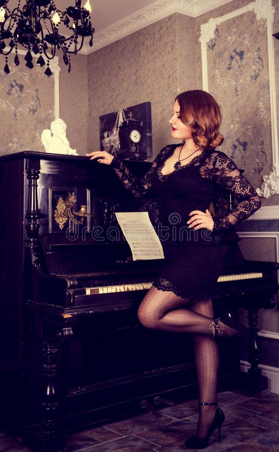 Elegant young woman in black dress posing near the piano. Beautiful woman in black dress and piano. royalty free stock images