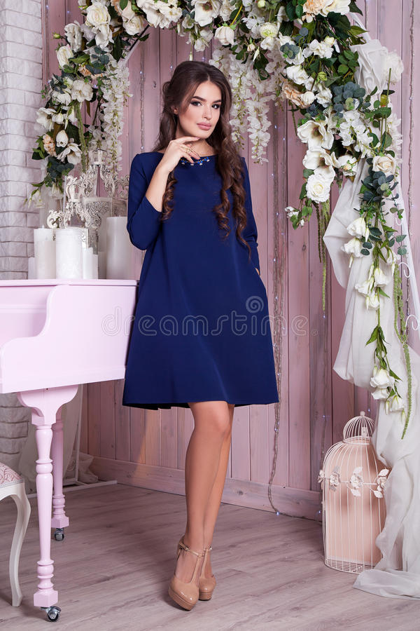 Elegant young woman in evening dress posing in interior. Fashion style portrait of a beautiful girl in interior. stock photos