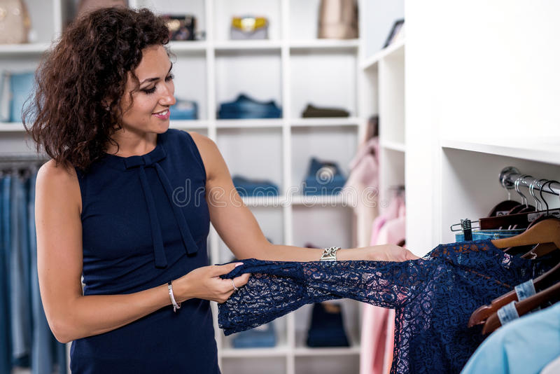 Elegant young woman looking for a new dress in clothing store stock photos