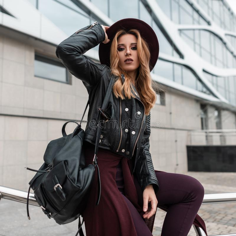 Elegant young woman with red hair in a black jacket with a leather backpack in trendy pants with a cape at the waist sits stock photos