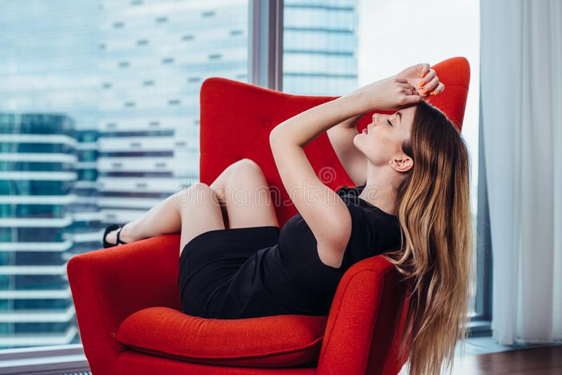 Elegant young woman relaxing on red stylish armchair in luxurious apartment stock photo