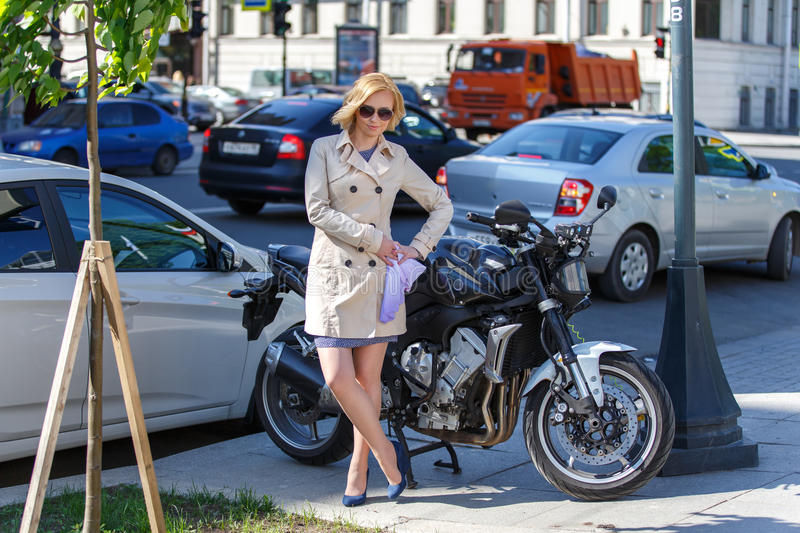 Elegant young woman in sun glasses near sport bike on the street stock photo