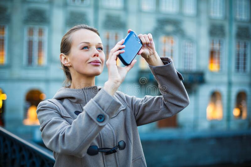Elegant, young woman taking a photo with her cell phone camera royalty free stock images