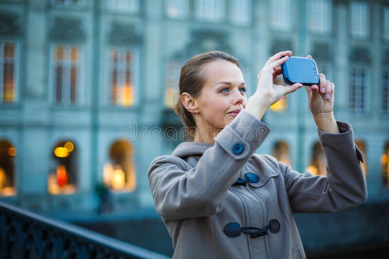 Elegant, young woman taking a photo with her cell phone camera stock photos