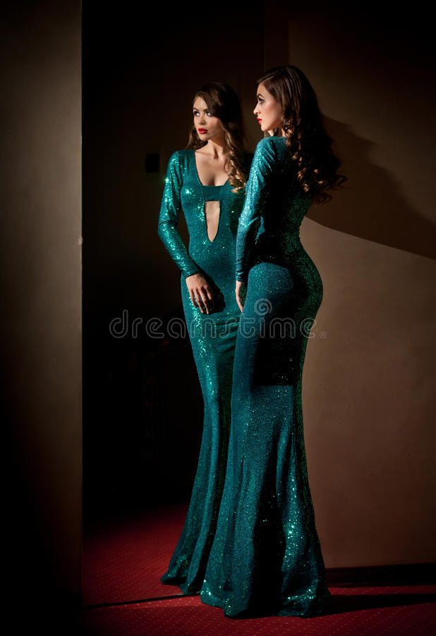 Elegant young woman in turquoise long dress looking into a large mirror, side view. Beautiful slim girl with creative hairstyle stock photo