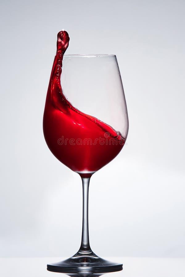 Elegant zuiver wijnglas met golf van helder rode wijn die zich tegen lichte achtergrond met neer bezinning bevinden in royalty-vrije stock foto's