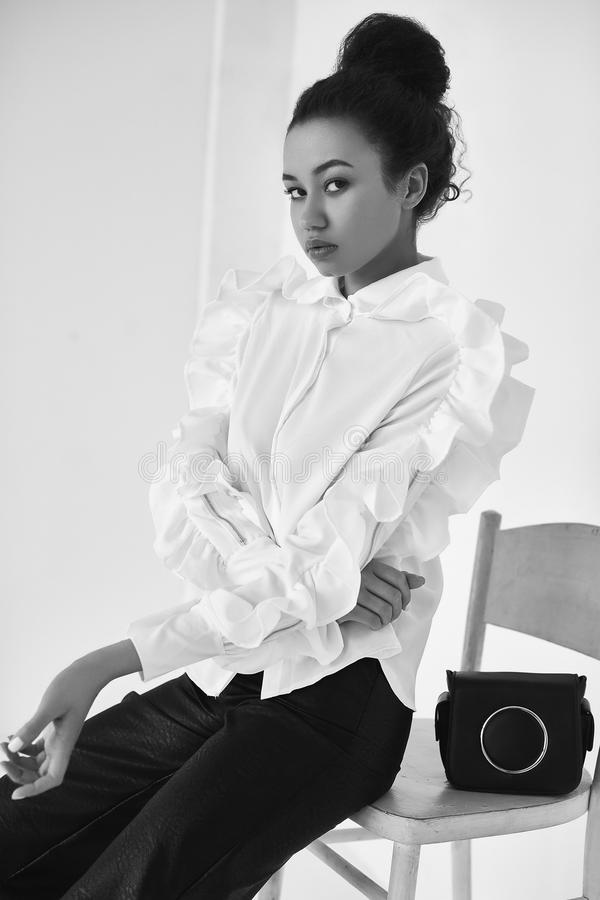 Elegant zwarte met krullend haar in modieus pak stock foto