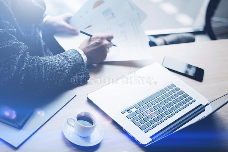 Eleganta bankrörelsen finansierar analytikeren som arbetar på det soliga kontoret på bärbara datorn, medan sitta på trätabellen A arkivbilder