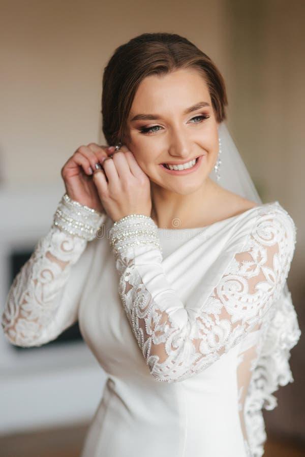Eleganta brudkläderörhängen Charma kvinnan i härlig bröllopsklänning arkivbild