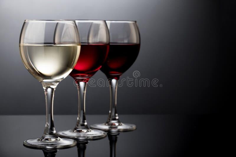 Eleganta exponeringsglas för rött, rosa och vitt vin i en svart bakgrund arkivbild