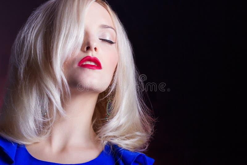 Eleganta härliga kvinnor som är blonda med röda kanter i en blå klänning i studion royaltyfria bilder