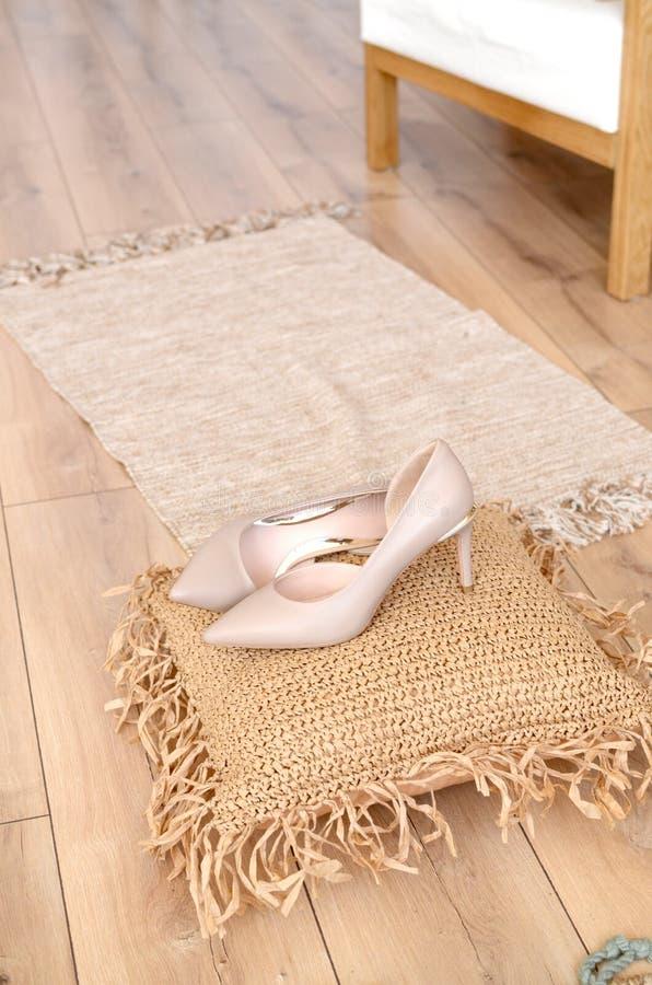 Eleganta läderkvinnors för beigea hög-heeled skor skor på skor för en häl för träbakgrund ljusa glansiga på en kudde av royaltyfria foton