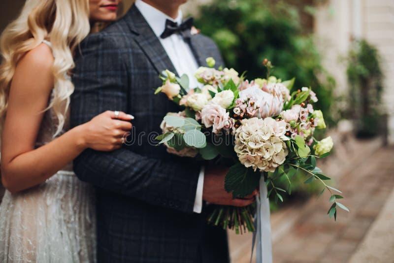 Eleganta par av blondiebruden och den stilfulla brudgummen som omfamnar och rymmer blommor royaltyfri fotografi