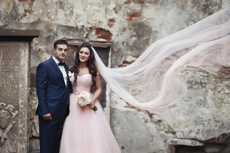 Eleganta par av nygifta personer som framme poserar av gammal kyrklig vägg w royaltyfri fotografi