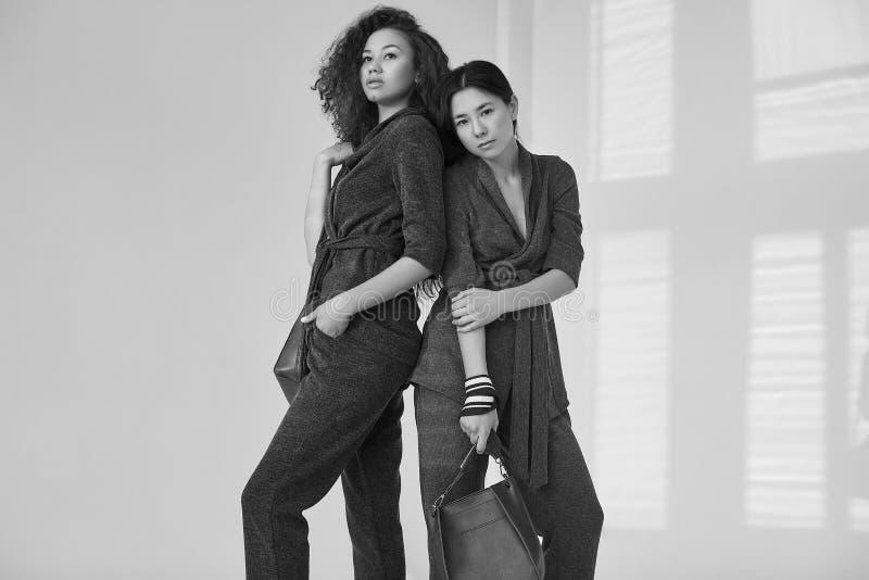 Eleganta par av svarta och asiatiska kvinnor i innegrejgräsplan och royaltyfria foton