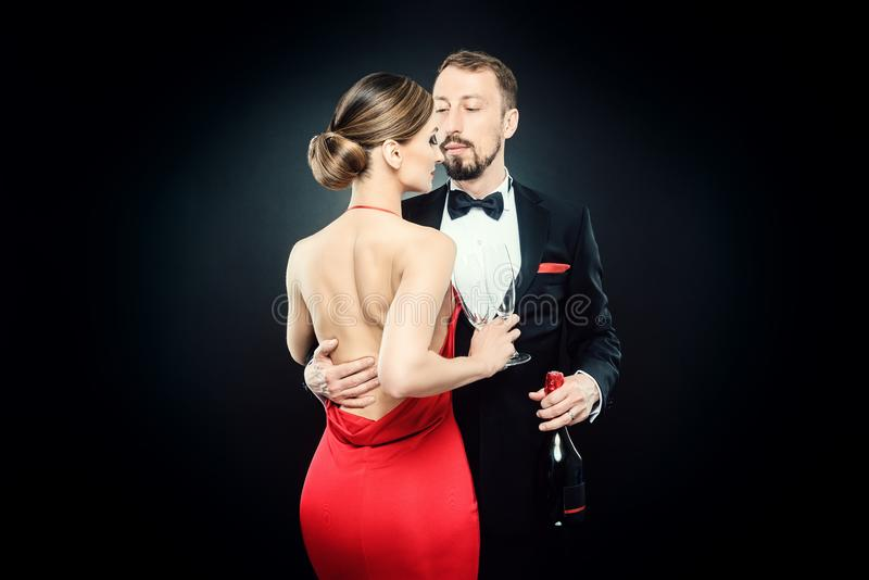 Eleganta par i aftonklänningen som omfamnar sig som är förälskad arkivfoto