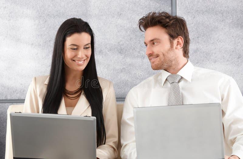 Eleganta par som sitter på sofaen genom att använda bärbar dator royaltyfri foto