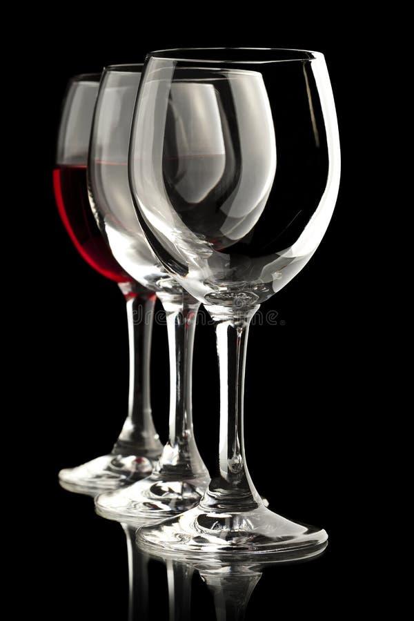 Eleganta vinexponeringsglas med ett mycket av rött vin arkivbilder