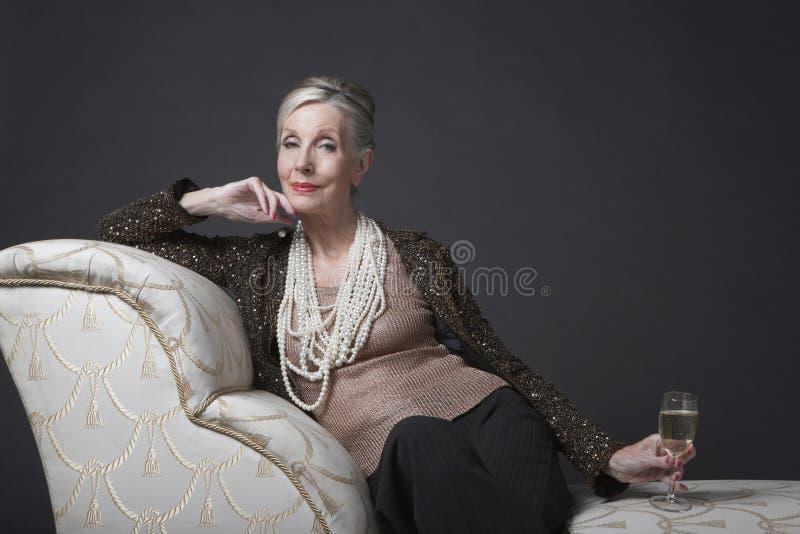 Elegante ältere Frau auf Chaise Lounge With Champagne lizenzfreie stockfotos