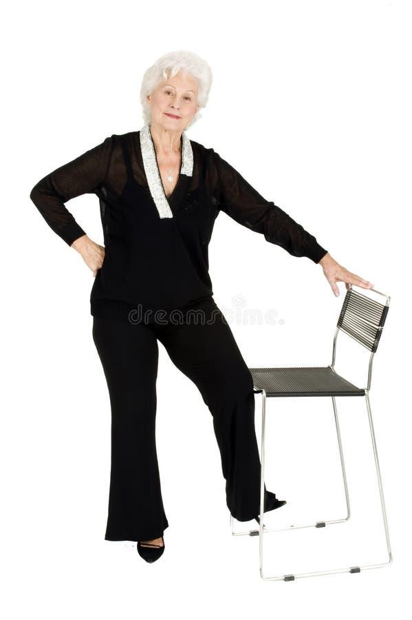 Elegante ältere Frau, die nahe einem Stuhl steht lizenzfreie stockfotografie