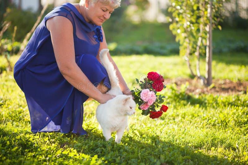 Elegante ältere Frau draußen mit Rosen und Katze lizenzfreie stockfotos