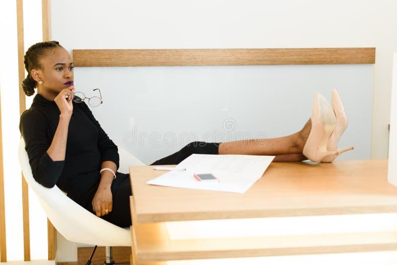 Elegante afrikanische oder schwarze amerikanische Geschäftsfrau, die Gläser, sitzend mit den Beinen in den beige Stiletten halten stockfoto