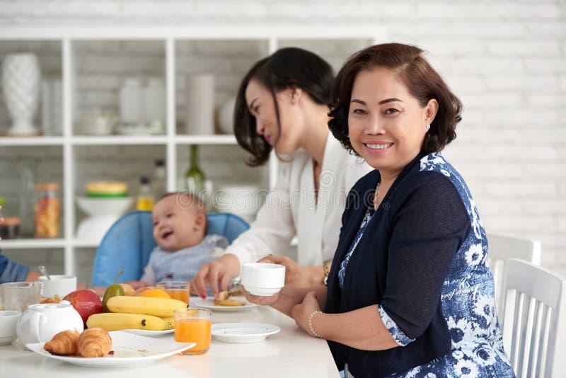 Elegante Asiatin am Frühstückstische mit Familie stockfotos