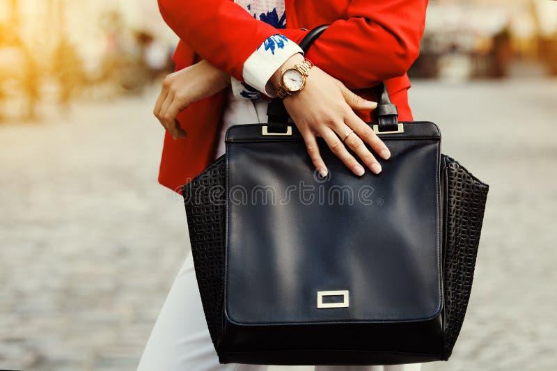 Elegante Ausstattung Abschluss oben Schwarze Ledertaschehandtasche in den Händen der stilvollen Geschäftsfrau Modernes Mädchen au stockfotografie